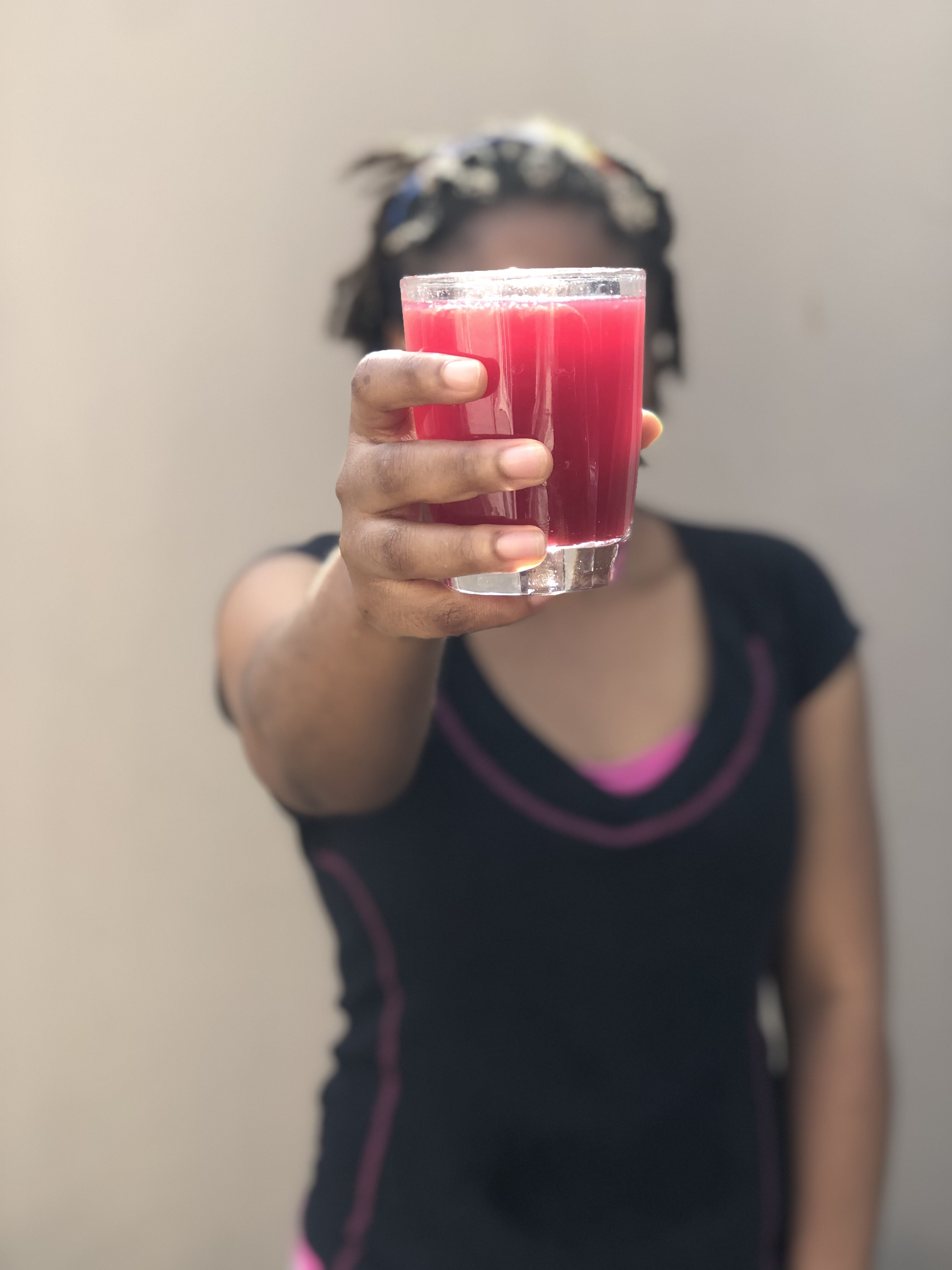 Quintessential Faith holding a cup of healthy zobo drink